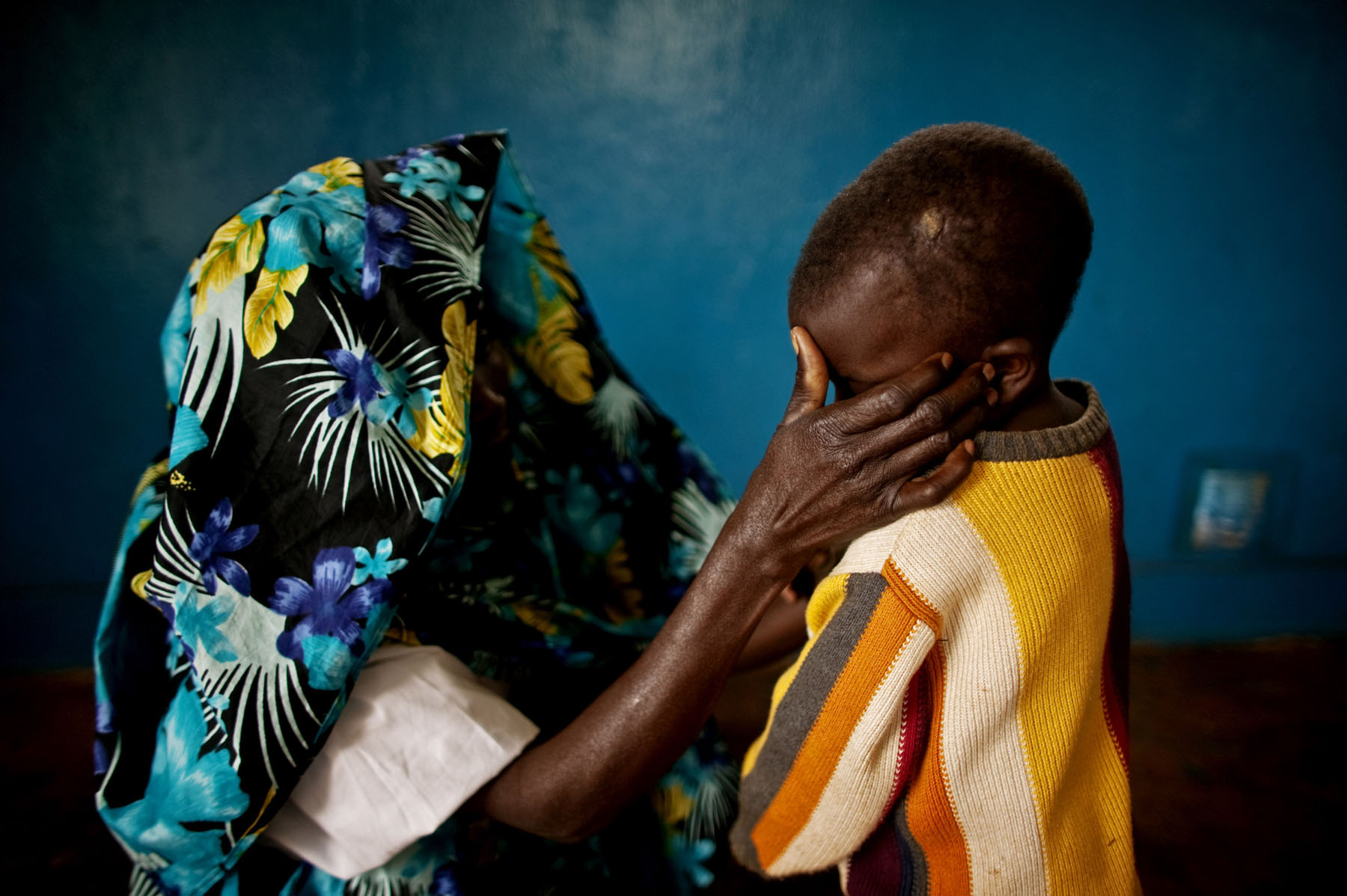A mass rape victim and her son in the town of Fizi. Her son suffered a head wound (pictured here) when soldiers threw him to the ground before raping and beating his mother. After posing for a portrait on her own, this woman insisted that I photograph her son. She seemed more concerned with his suffering than with her own.