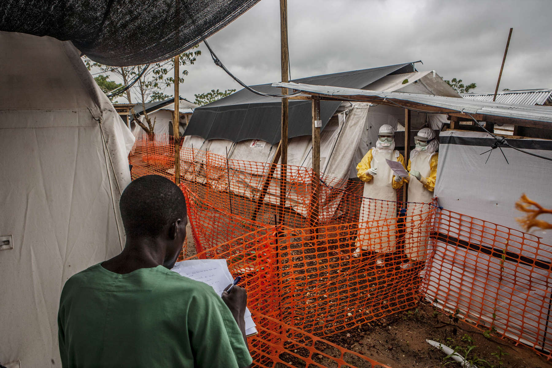 Doctors Without Borders medical staff discuss patient status across an established safety cordon in an Ebola treatment center in Kailahun, Sierra Leone on Sunday, August 17, 2014. Those in masks stand in the {quote}high risk{quote} zone where highly contagious Ebola victims receive treatment. (Pete Muller/Prime for the Washington Post)