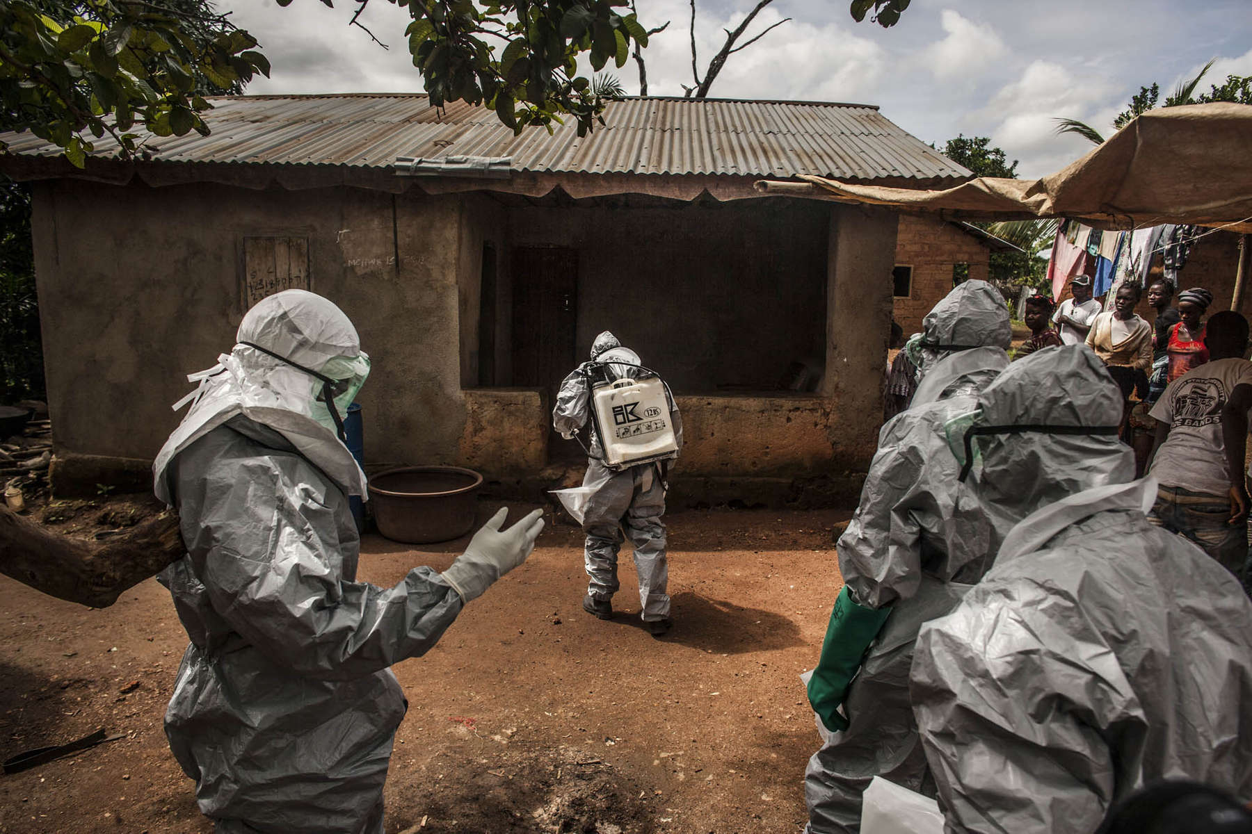 Members of a Red Cross burial team don personal protective equipment and spray chlorine as they prepare to enter the home of a woman suspected of dying of Ebola in the village of Dia on Monday, August 18, 2014. The government of Sierra Leone mandates that all deaths in which the cause is unclear be treated as potential Ebola cases. Contact with the bodies of Ebola victims is a leading cause of virus transmission. (Pete Muller/Prime for the Washington Post)