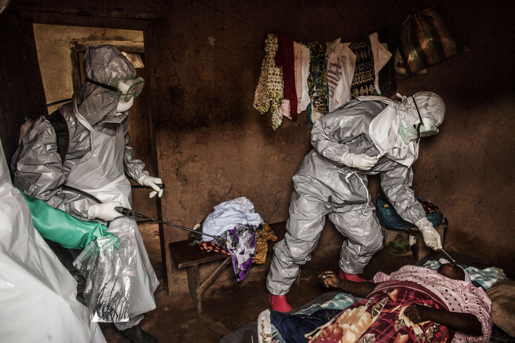 Members of a Red Cross burial team take samples from a   woman suspected of dying of Ebola in the village of Dia on Monday, August 18, 2014. So-called {quote}safe burials,{quote} conducted by the International Federation of the Red Cross, are conducted in accordance with rigorous safety procedures. The dead bodies of Ebola victims are extremely infectious.(Pete Muller/Prime for the Washington Post)