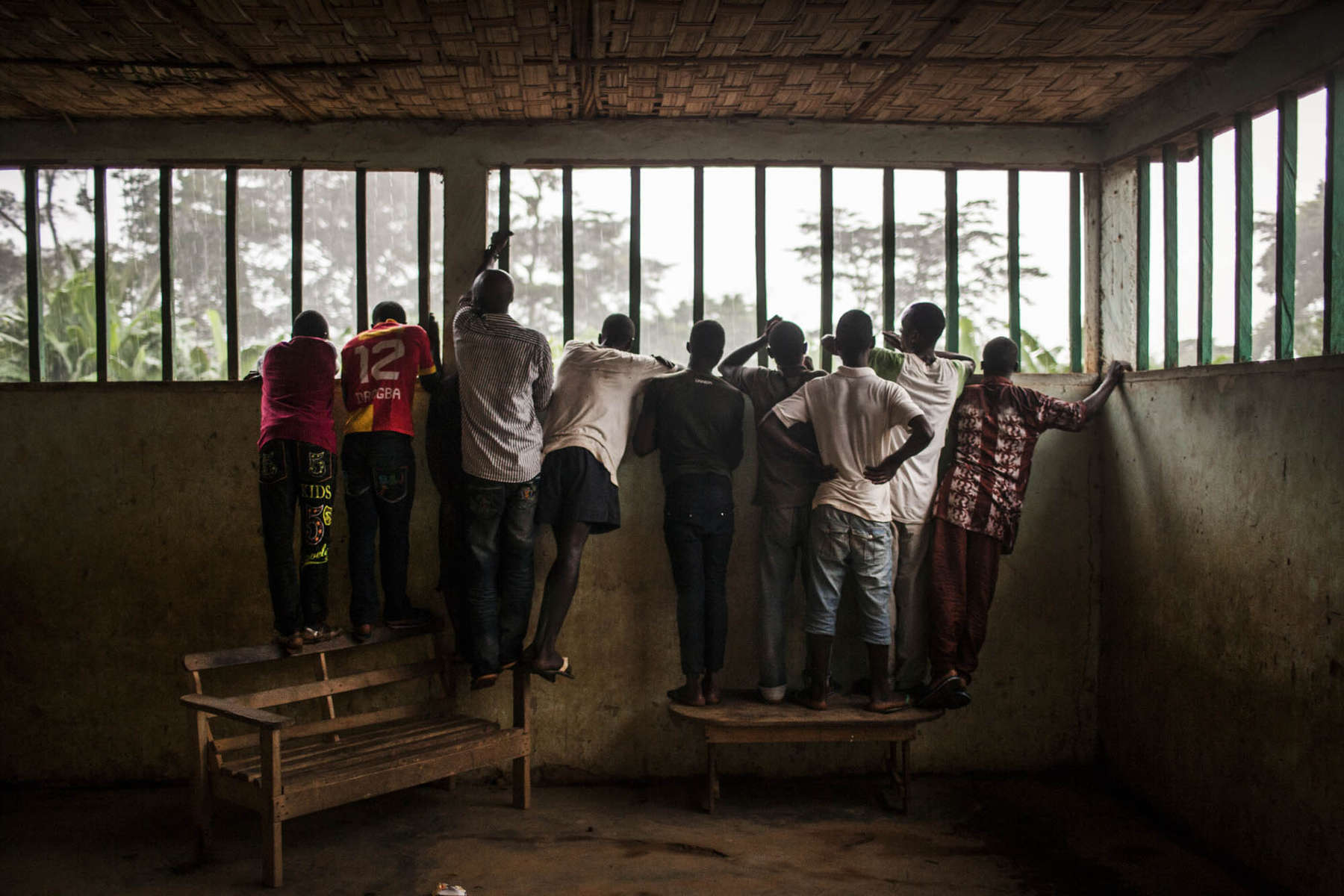 Residents of the village of Sengema, Sierra Leone gather inside a school house to watch Red Cross workers prepare the body of a many suspected of dying of Ebola   on Saturday, August 18, 2014. (Pete Muller/Prime for the Washington Post)