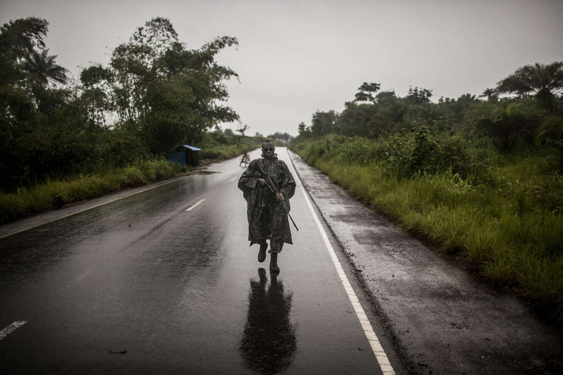 A Sierra Leonean solider mans a checkpoint on the road from Freetown to Kenema on Friday, August 22, 2014. Sierra Leone's police and military have established numerous checkpoints on roads leading into and out of Ebola-affected areas. Only trucks carrying essential goods and persons with government issued permission may cross the checkpoints.  (Pete Muller/Prime for the Washington Post) (Pete Muller/Prime for the Washington Post)