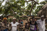 Community members in the village of Dia, eastern Sierra Leone, look on as a Red Cross burial team prepares to enter the home of a woman suspected of dying of Ebola on  Monday, August 18, 2014. Family and community members are encouraged not to touch the bodies of those suspected of dying from Ebola as the bodies are highly contagious. This aspect of the virus has seriously disrupted traditional funeral ceremonies.(Pete Muller/Prime for the Washington Post)
