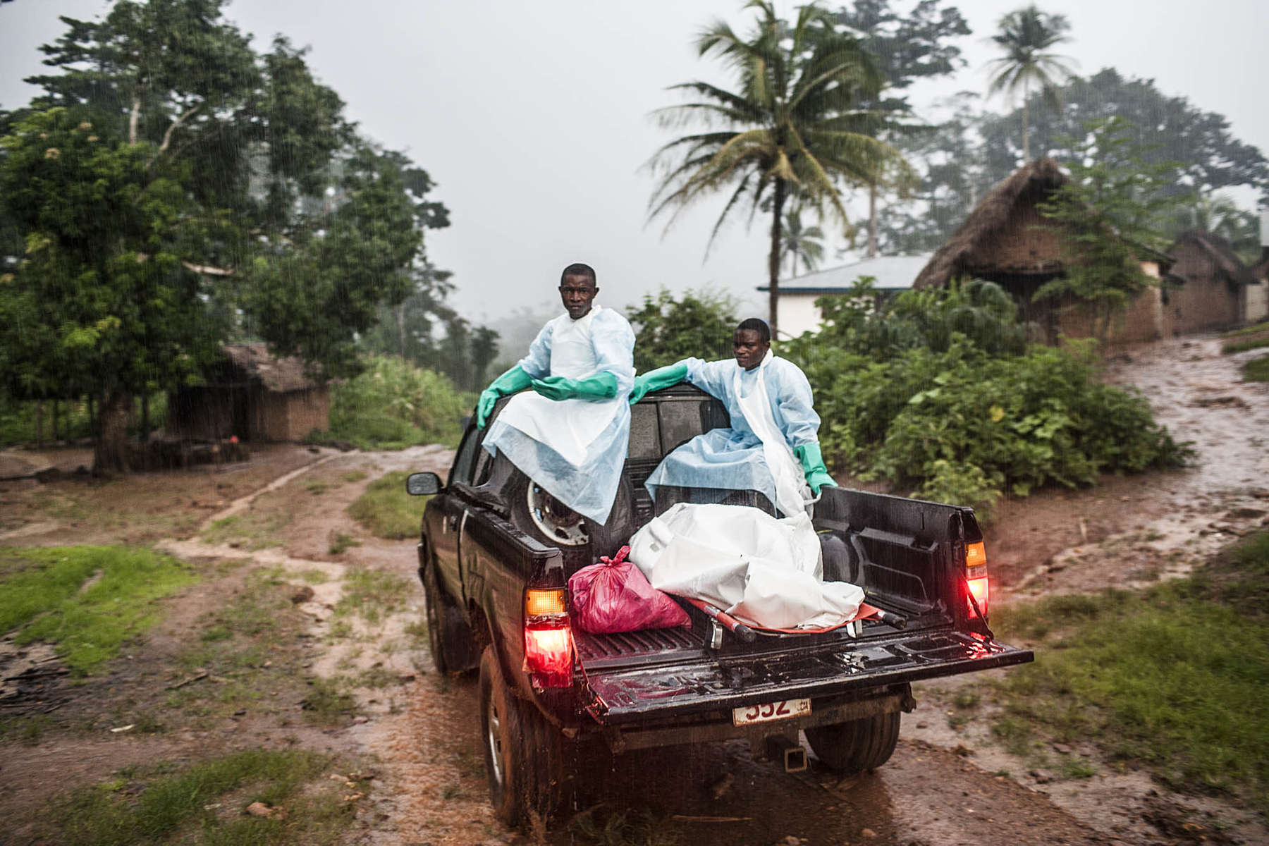 Red Cross burial workers transport the body of a man suspected of dying from Ebola in the village of Sengema, Sierra Leone on Saturday, August 18, 2014. Bodies are buried away from residential areas in a bid to ensure that the infection will not spread. (Pete Muller/Prime for the Washington Post)