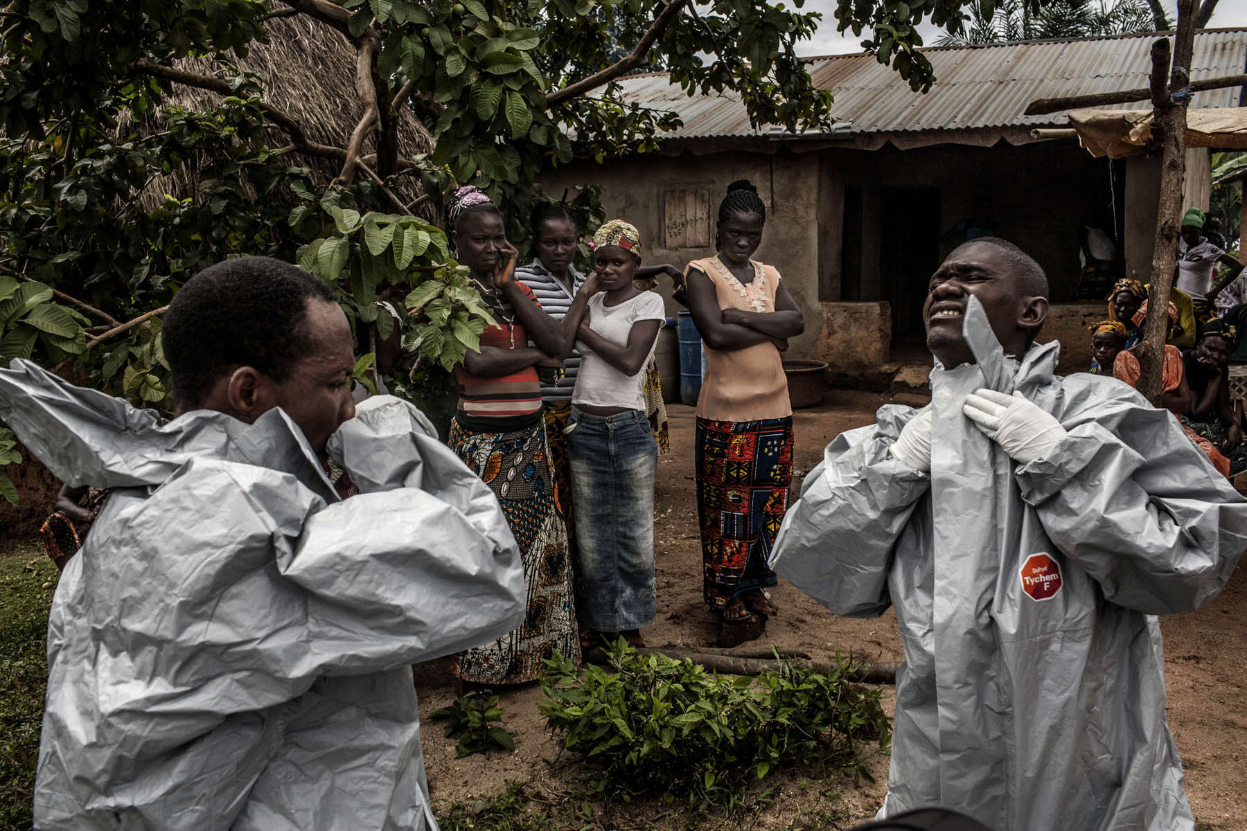 Members of a Red Cross burial team put on personal protective equipment before entering the home of a woman suspected of dying of Ebola in the village of Dia on Monday, August 18, 2014. So-called {quote}safe burials,{quote} conducted by the International Federation of the Red Cross, are conducted in accordance with rigorous safety procedures. The dead bodies of Ebola victims are extremely infectious. (Pete Muller/Prime for the Washington Post)