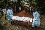 Members of a Red Cross burial team prepare to bury the body of a woman suspected of dying of Ebola in the village of Dia, Sierra Leone, on Monday, August 18, 2014.  (Pete Muller/Prime for the Washington Post)