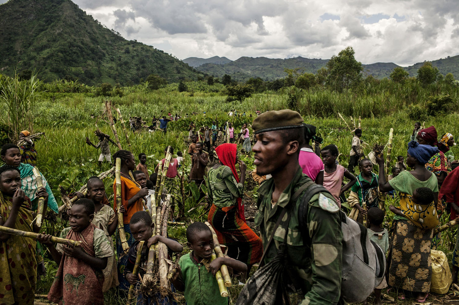 Civilians chop down sugar cane to pass along to Congolese soldiers as they advance up the mountainous road toward Bunagana, the last remaining stronghold of the M-23 rebels on Wednesday.