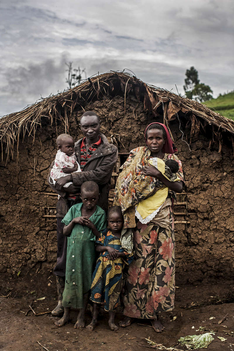 Marisiyana Bizimana, 30 (right) her husband, Kanyeshamba Gwagitare, 40, and their four children stand for a portrait outside their home in Kivuye. The family took refuge in Kivuye after fleeing horrific violence committed by Mai Mai leader Cheka in their home village of Pinga.