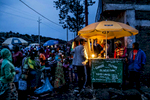 Not far from the frontline, Goma residents shop and charge their cell phones during the evening.