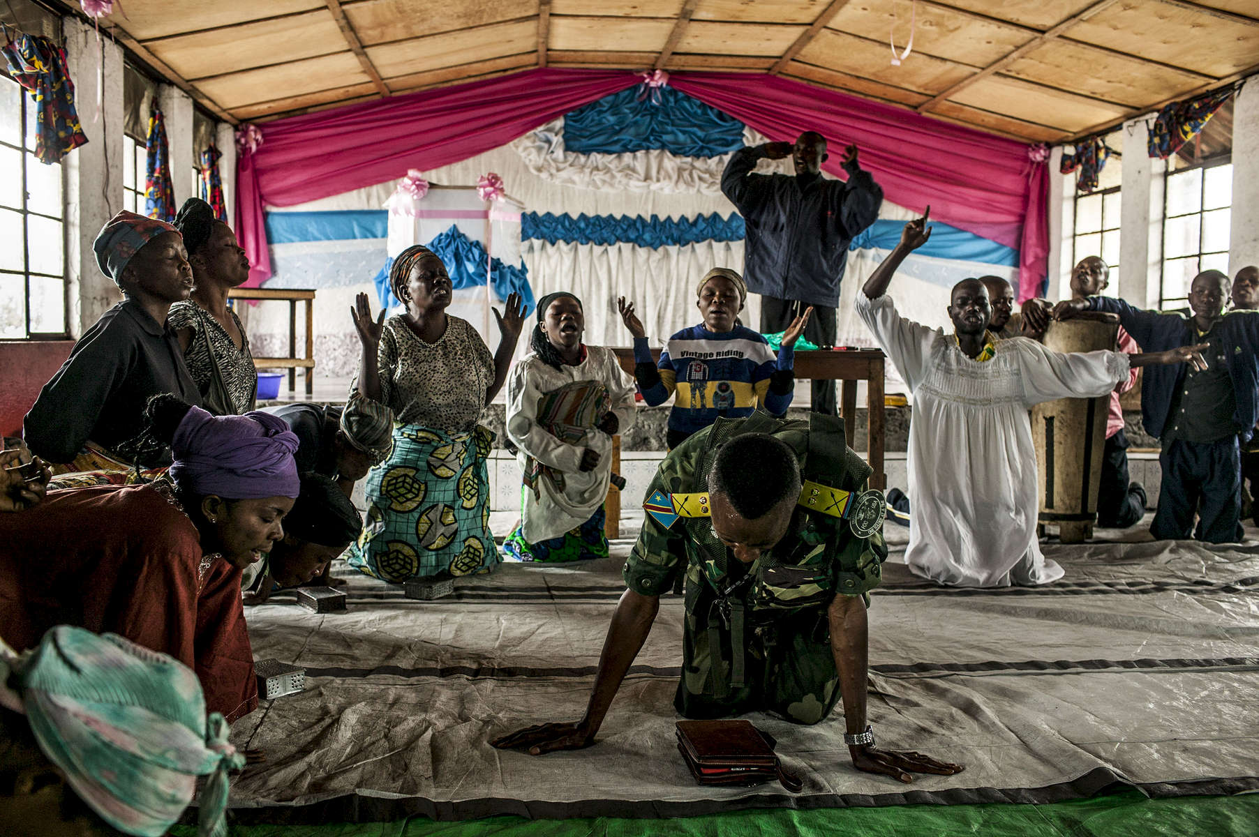 A military chaplain conducts a prayer ceremony for the family members of soldiers inside the main military camp in Goma.