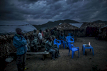 A unit of the Congolese army passes time in the evening by watching a movie on a laptop at a base outside of Kitchanga, eastern Congo.