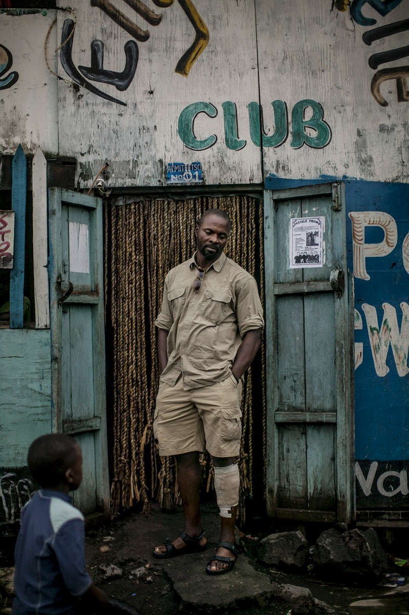 Eagle, a Congolese solider, stands outside a nightclub in the city of Sake, in eastern Congo. The bandage on his left leg covers wounds he sustained during battles against the M-23 one week before this image was made. He oversees the checkpoint between Sake and Goma, a critical point in the mineral transportation route. A father of five who often goes months without being paid by the government, Eagle admits to extorting fees from transporters at his checkpoint. {quote}How am I supposed to feed my children,{quote} he laments.