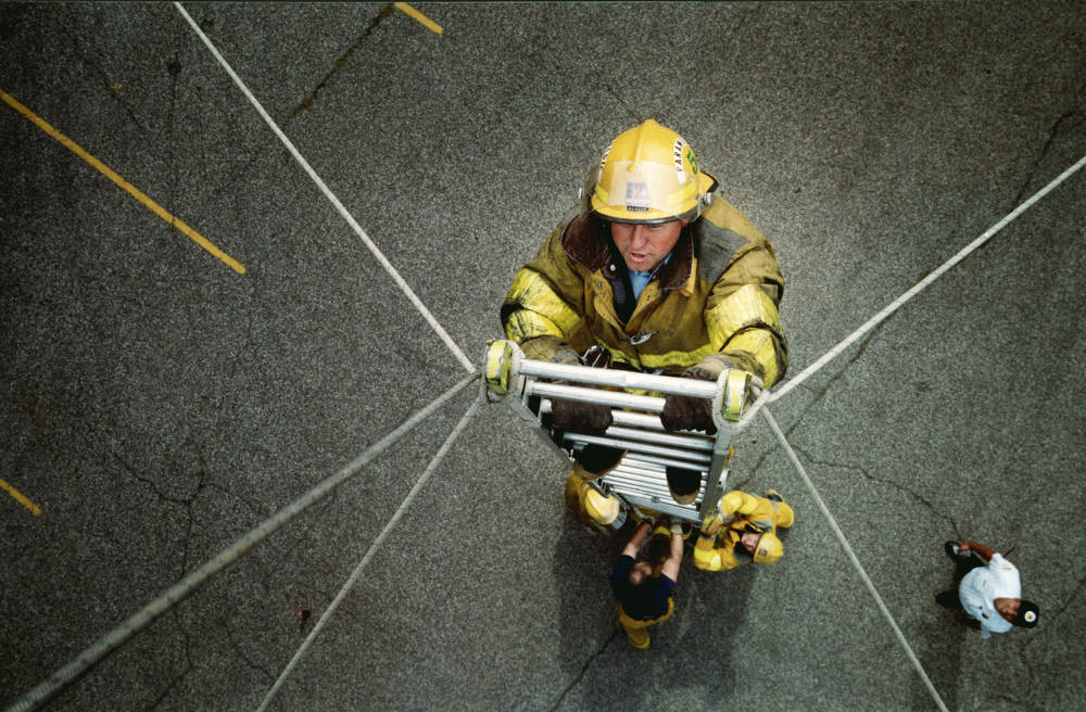 A firefighter climbs a ladder held up by just ropes as a trust building exercise.