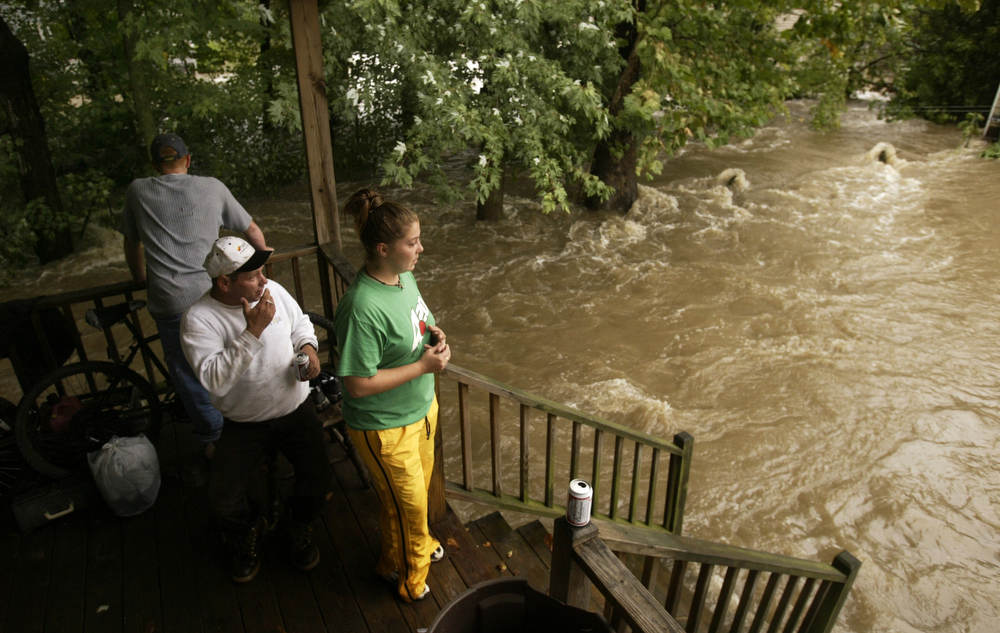 Tom Freeman, Donald Kise Jr. (sitting) and Autumn Widuto watch the Blair Creek swirl around Kise's home on Douglass in Blairstown during  flooding in Blairstown from Hurricaine Ivan.