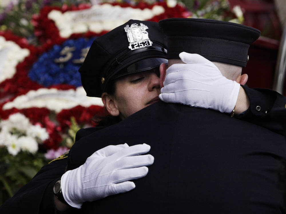 Newark Police officer Brandi McTighe embraces her brother and Newark firefighter Shannon McTighe in front of a Newark firetruck carrying flowers in the shape of a firefightrers badge after the funeral for  Newark firefighter and biker Ray Martinez at St. Lucy's Church in Newark on Saturday.