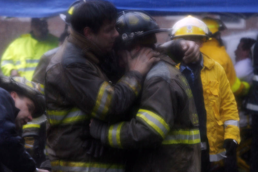 A firefighter is comforted after fire destroyed the inside of the Holmes Marshall fire station which went to four alarms.