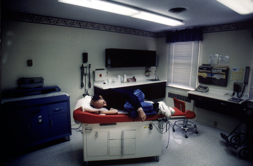 Peter lays in the doctors examining room while waiting for the doctor to show up for his check up.