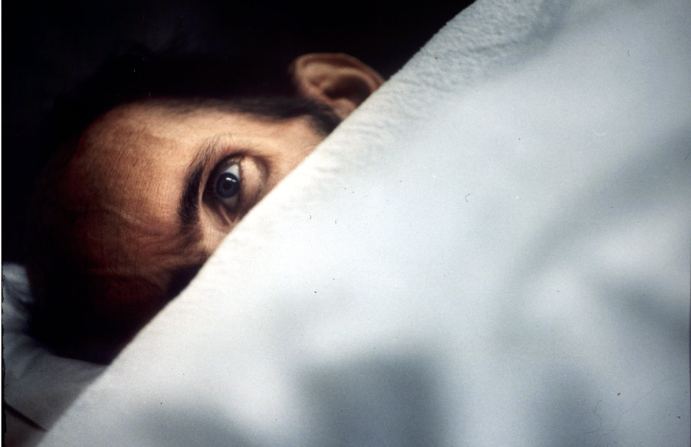 Peering out from behind his hospital bed sheet Peter drops into thought.