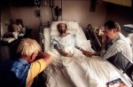 Volunteers sit with Peter as he nears death at the hospital.