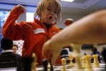 Ethan Cornett, 8 from Berkley Heights enjoys a move he made while playing against Sage Overbay 5, during the beginners chess class with Martin Sobin at the Bernardsville library.