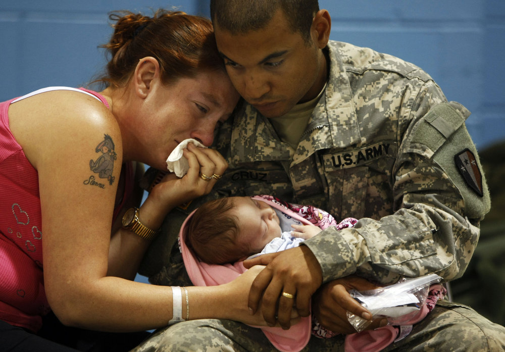 Carmelo Cruz of Willingboro holds his two week old daughter Athena Cruz  with his wife Angeline Cruz  during the last visiting time   at the Freehold National Guard armory in Freehold.