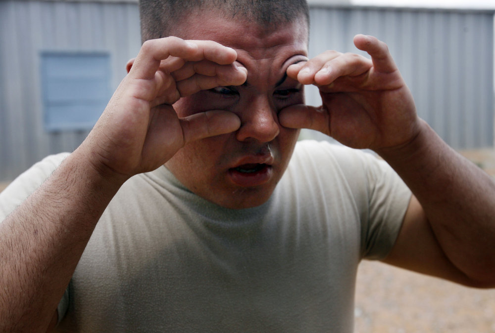 PFC Amariel Perez, D company 1st 114th from  Vineland New Jersy national guard are training for their upcoming deployment to Iraq at McGregor range in New Mexico. Here he pries his eye open looking for relief after being sprayed with Oleoresin Capsicum (pepper spray on steriods).