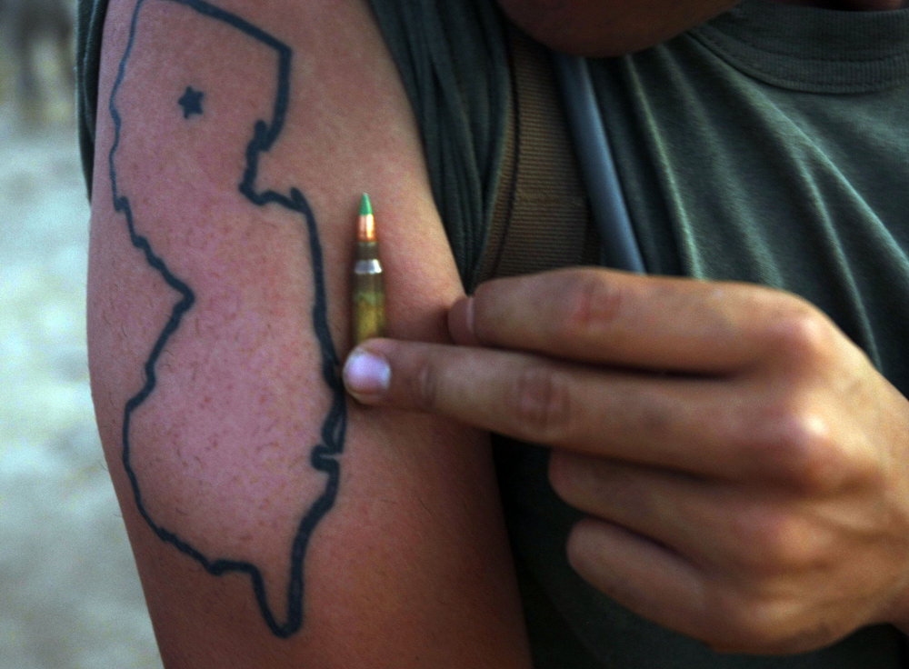 Lance Corporal Giancarlo Bruzzese of Rockaway Township holds a bullet next to his Jersey tattoo.