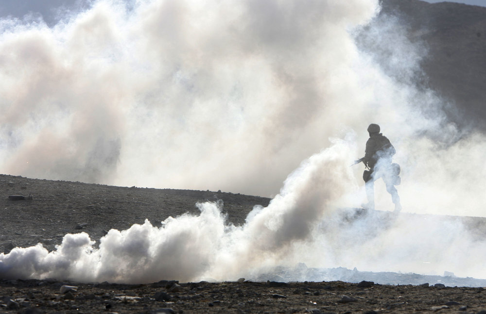 A Marine makes his way through smoke during an assault on a trench during a live fire exercies. New Jersey Marines in training at the Marine Air Ground Task Force Training command at Twentynine Palms, California.