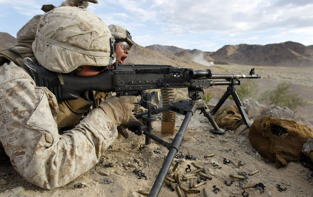 Lance Corporal Dionnys Feliz encourages Lance Corporal Michael Szymanski while firing his machine gun during a live fire exercise.