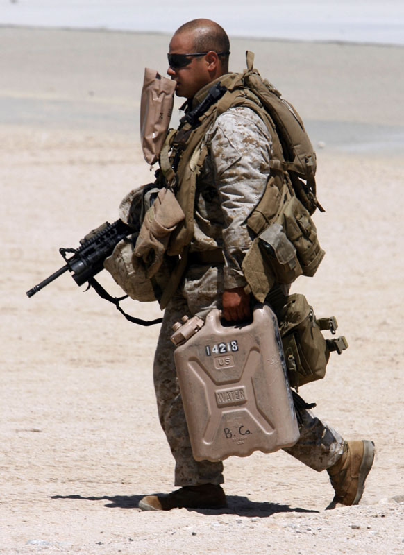 A marine carries his MRE in his teeth while wearing body armour, weapon and carrying a water container in the 108 degree heat of the Mojave desert. New Jersey Marines in training at the Marine Air Ground Task Force Training command at Twentynine Palms.