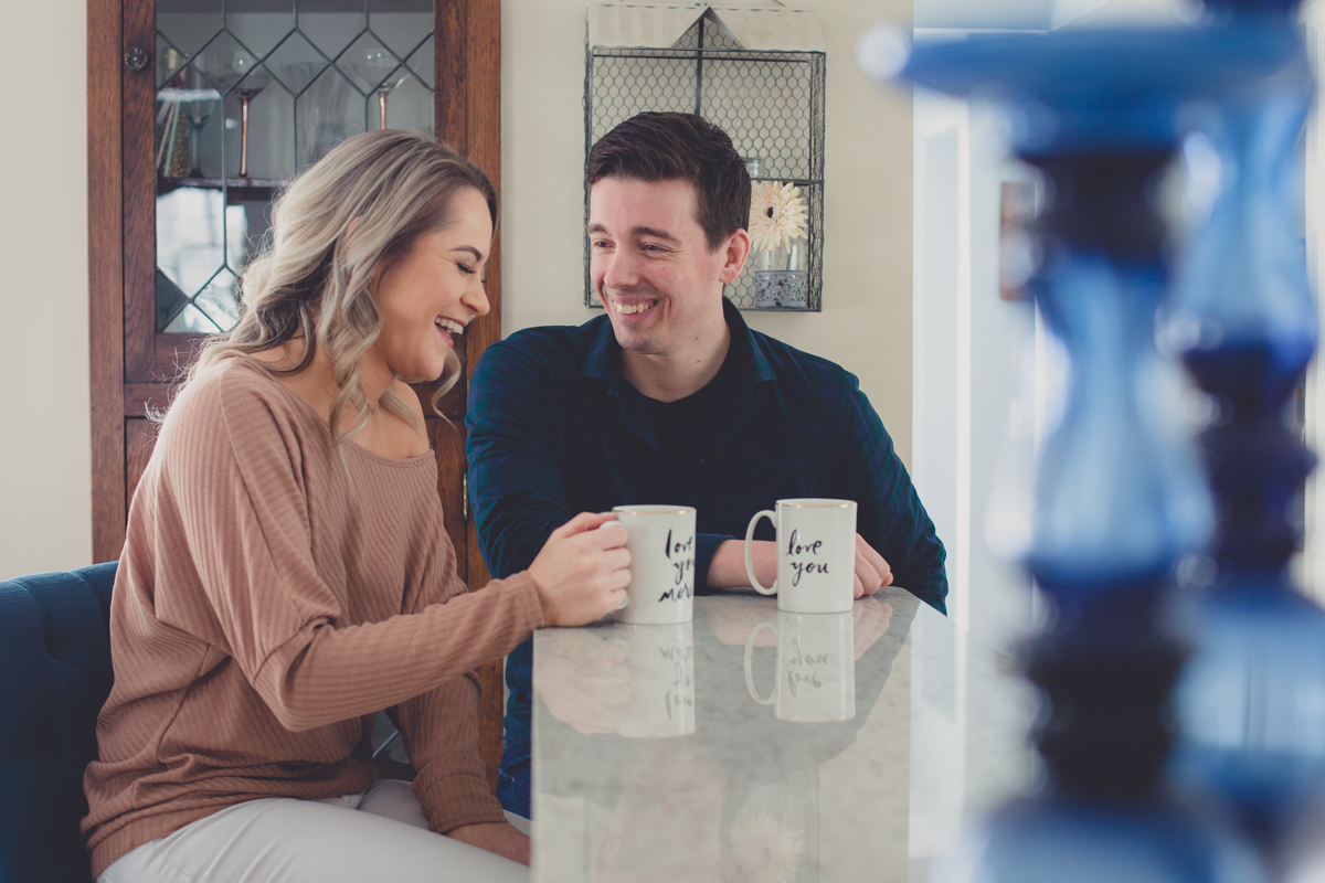 bride and groom sip coffee at kitchen counter during in home engagement photography session in Buffalo, NY