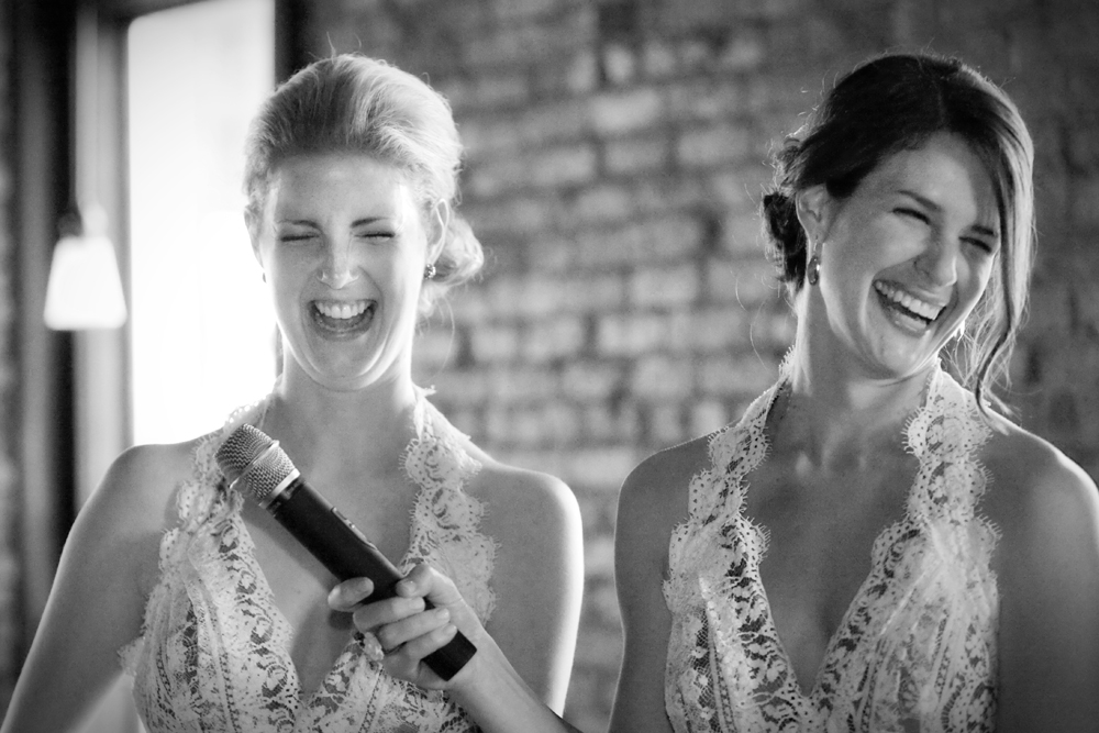 Bridesmaids laugh while delivering speech at wedding at Pearl St. Grill and Brewery in Buffalo, NY.
