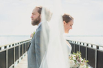 bride and groom stand back to back on gallagher pier at the Outer Harbor in Buffalo, NY