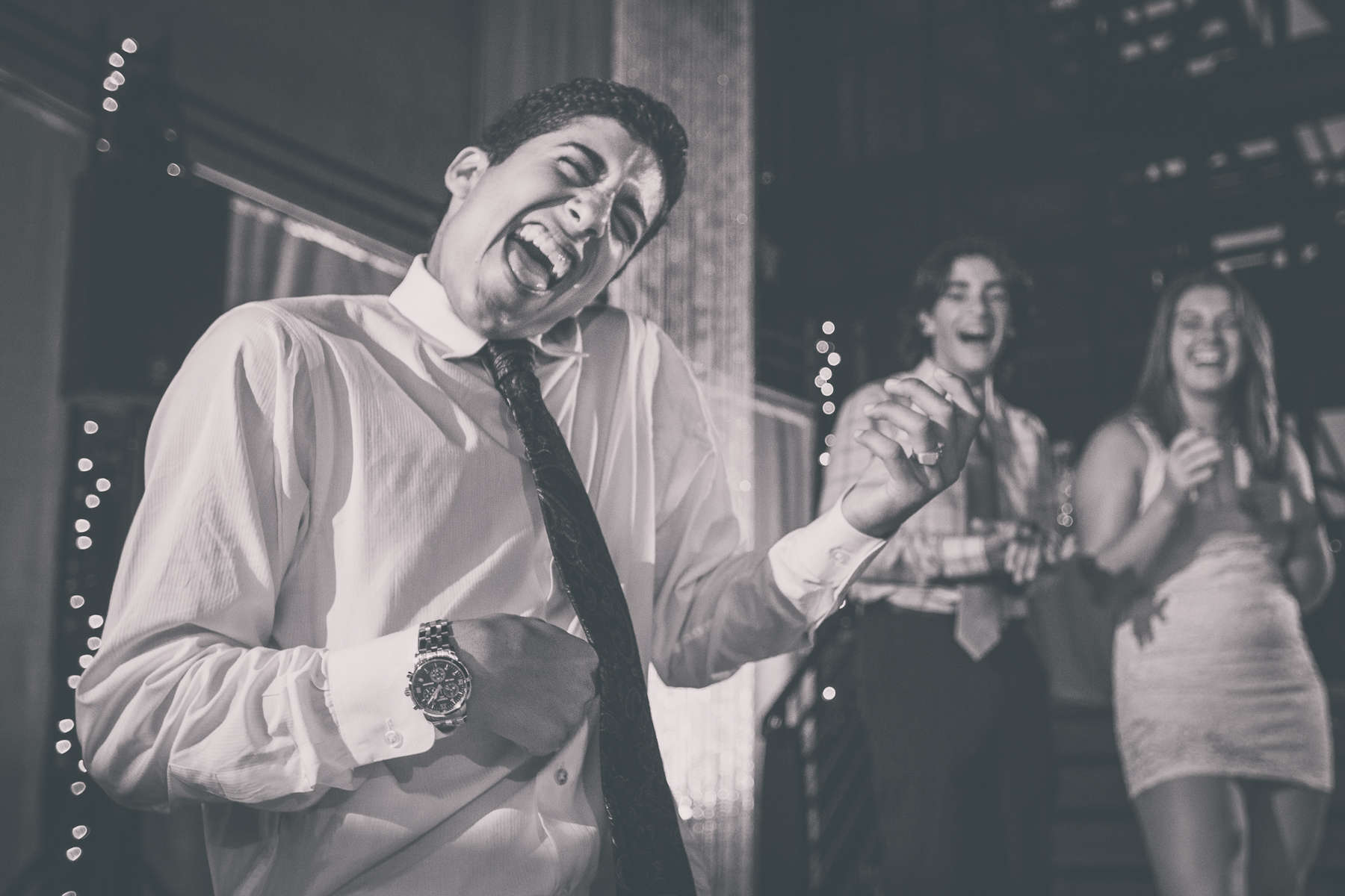 photograph of wedding guest dancing with air guitar at reception at High Falls in Rochester, NY