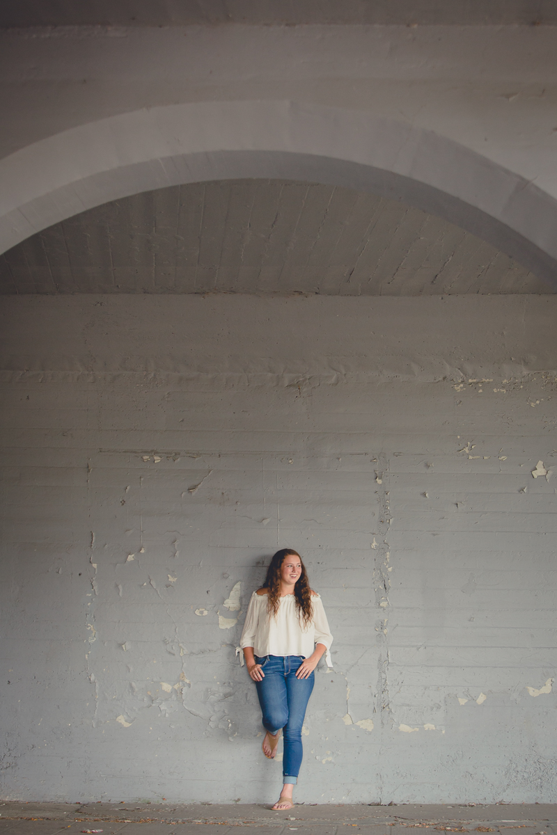senior portrait by photographer Lindsay DeDario of Southwestern high school student under overpass in Jamestown, a small city near Buffalo, NY in WNY