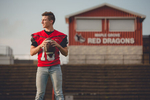 senior portrait by photographer Lindsay DeDario of maple grove high school student holding ball on football field in Bemus Point, a small town near Buffalo, NY in WNY