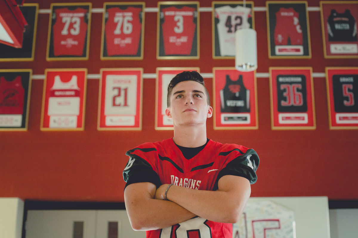 senior portrait by photographer Lindsay DeDario of maple grove high school student standing in front of hall of fame jerseys inside school in Bemus Point, a small town near Buffalo, NY in WNY