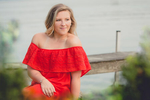senior portrait by photographer Lindsay DeDario of maple grove high school student sitting in red dress by dock overlooking Lake Chautaqua in Bemus Point, a small town near Buffalo, NY in WNY