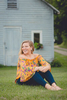 senior portrait by photographer Lindsay DeDario of maple grove high school student sitting in front of cottage in Bemus Point, a small town near Buffalo, NY in WNY