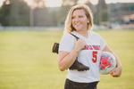 senior portrait by photographer Lindsay DeDario of maple grove high school student holding soccer ball and cleats in field in Bemus Point, a small town near Buffalo, NY in WNY