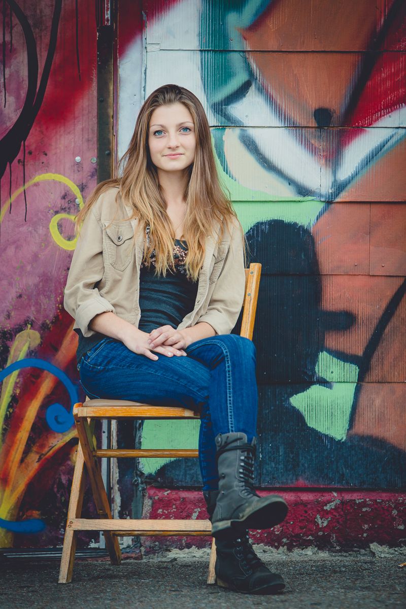 senior portrait by photographer Lindsay DeDario of East Aurora high school student sitting on chair in front of Mural in the Allentown section of Buffalo, NY in WNY