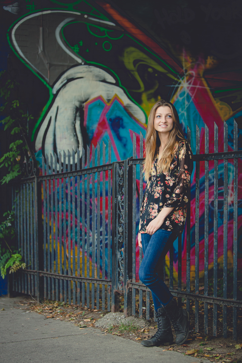 senior portrait by photographer Lindsay DeDario of East Aurora high school student leaning on iron gate in Allentown section of Buffalo, NY in WNY