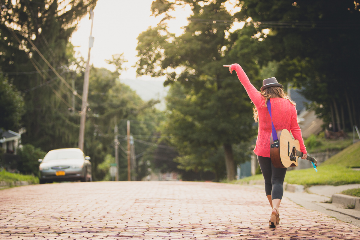 senior portrait by photographer Lindsay DeDario of Maple Grove high school student walking down cobble stone street while waving goodbye with guitar around shoulder in Jamestown, a small city near Buffalo, NY in WNY