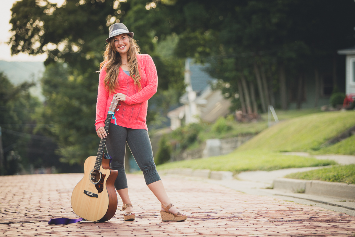 senior portrait by photographer Lindsay DeDario of Maple Grove high school student standing on cobble stone street with guitar in Jamestown, a small city near Buffalo, NY in WNY