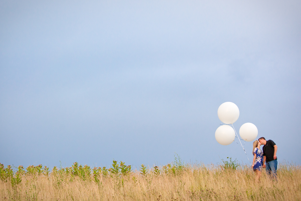 engagement photography in Buffalo NY of couple holding giant white balloons in field