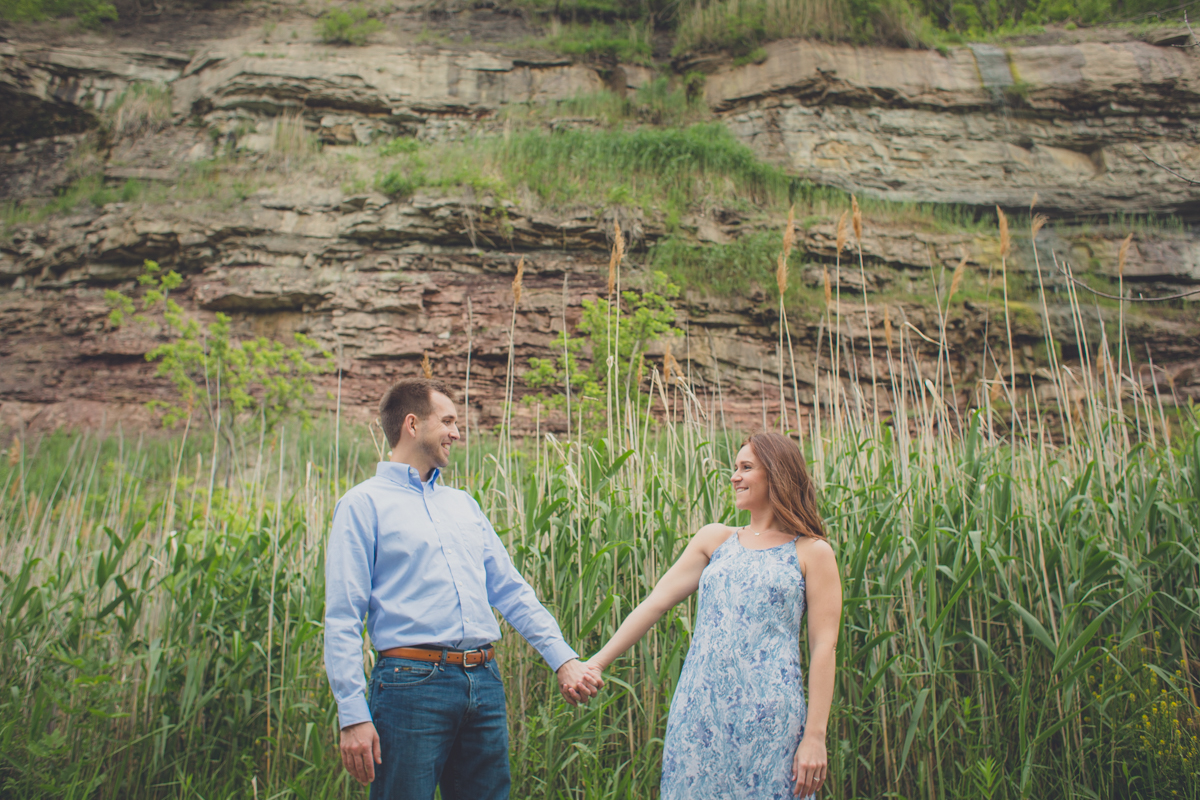 couple holds hands and smiles at each other on trail during wedding engagement portrait photography session at Artpark in Lewiston, NY