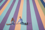 artpark wedding engagement photography of couple sitting together in colorful painted parking lot in Lewiston, NY