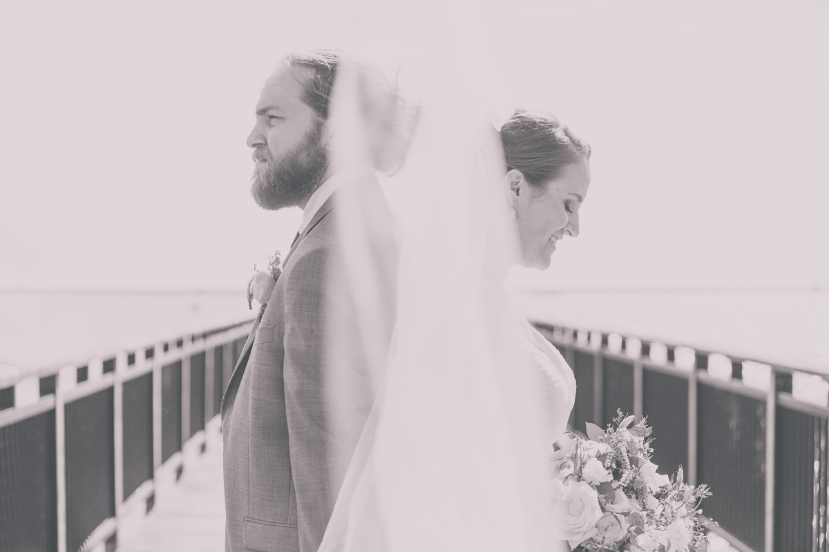 Black and white wedding photography of bride and groom standing on gallagher beach pier in Buffalo, NY.  The couple stand back to back with veil blowing in wind between them.