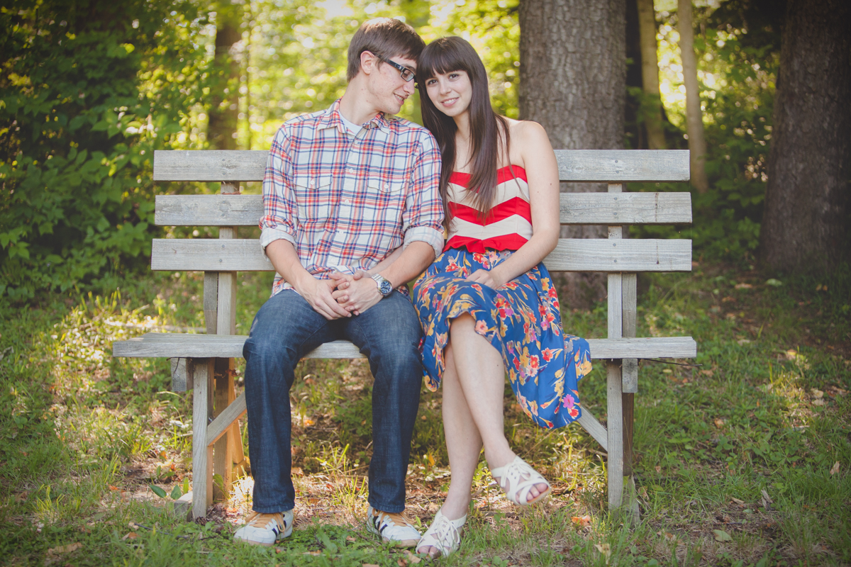 future groom and bride sit together on park bench during wedding engagement photography session in Buffalo, NY