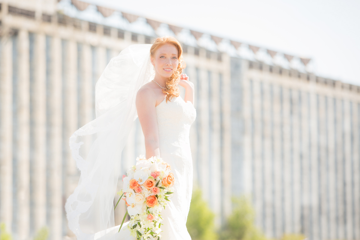 Wedding photography of bride standing on rocks at Gallagher Beach in front of grain elevators in Buffalo, NY